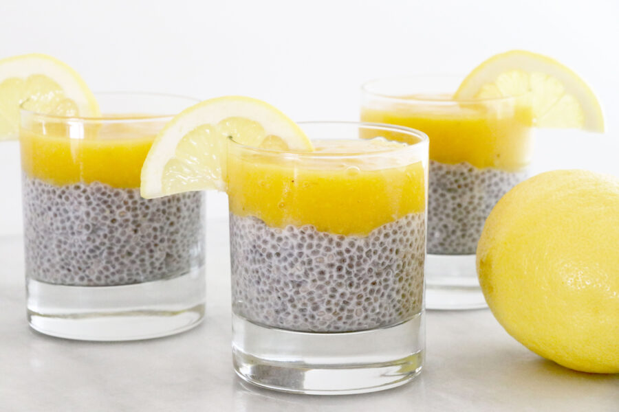 3 small glasses layered with chia pudding, lemon puree and lemon garnish.
