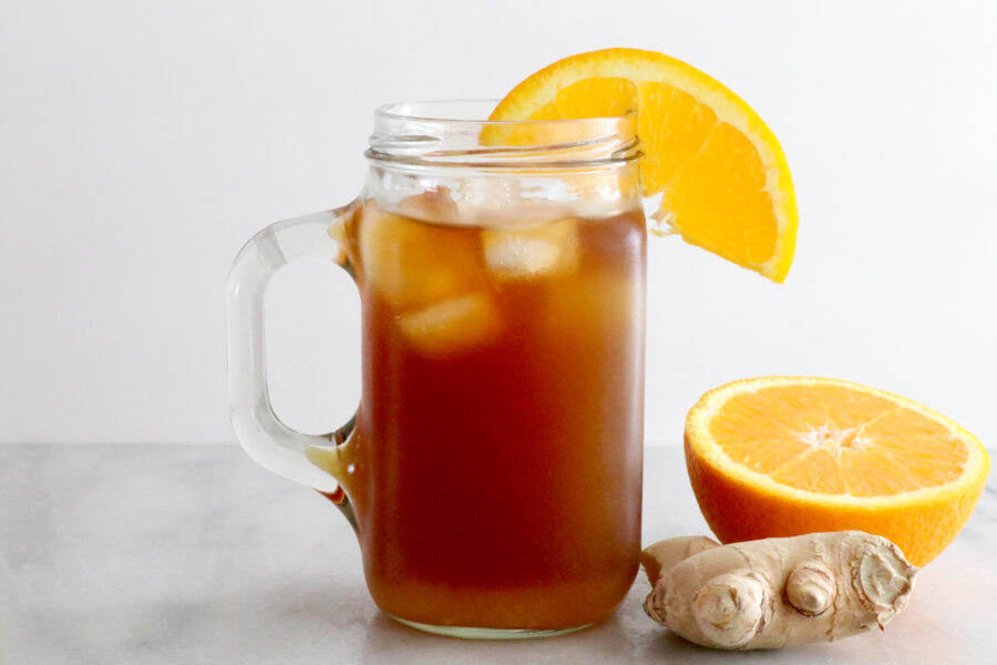 Glass in center of photo filled with cold brew, orange on glass and ginger next to glass.