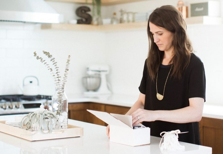 Woman in kitchen packaging a box of organic beauty products