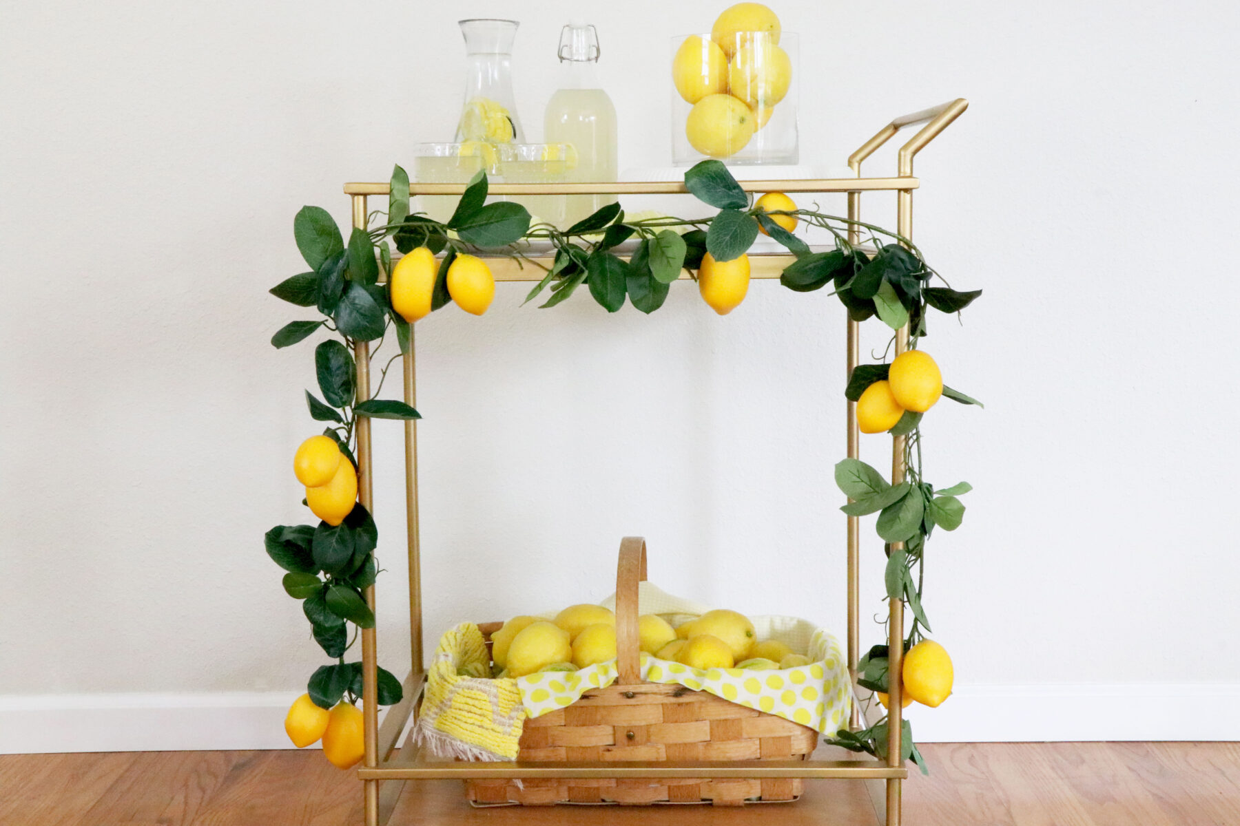 Drink cart in the middle of photo lined with a lemon garland, basket of lemons on the bottom shelf, and lemonade, cookies and a vase of lemons on the top.