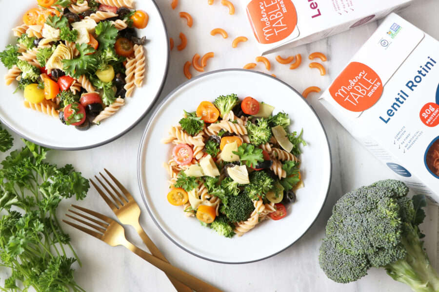 Two plates of Italian pasta salad in the center and upper left corner. Picture surrounded by broccoli, pasta salad packages, herbs and silverware.