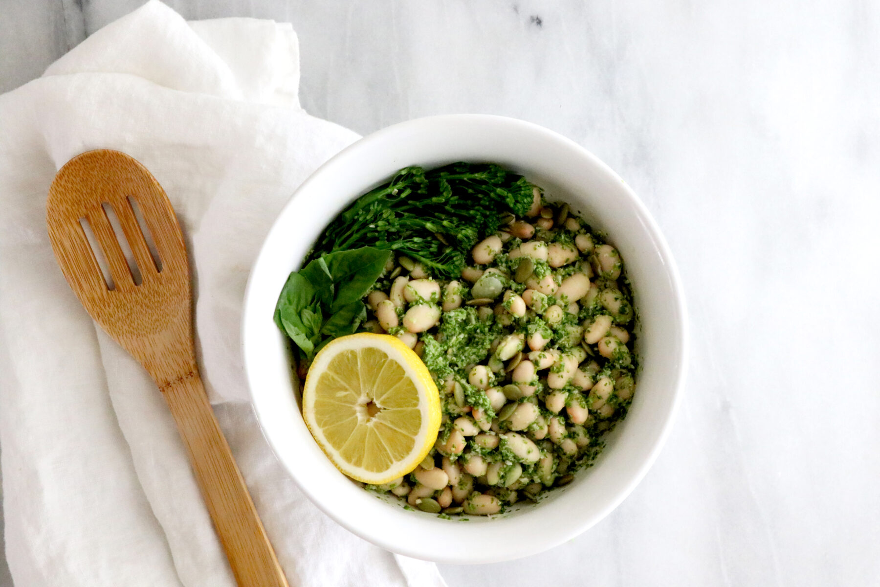 Bowl in center of photo filled with lemon broccolini pesto & beans. Spoon to the left of bowl on white napkin.