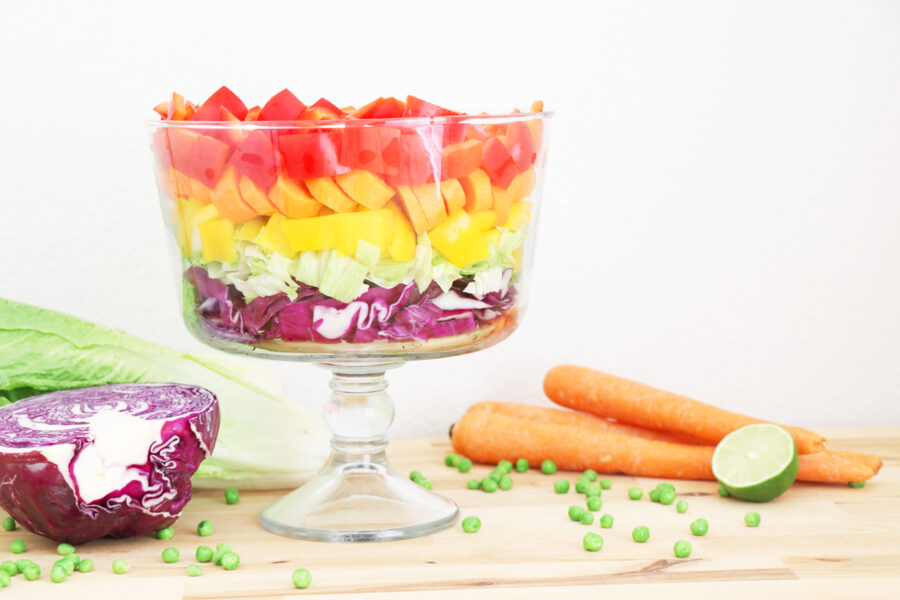 Trifile bowl containing layered rainbow salad on the left part of the photo. Carrots and lime on the right side of photo and purple cabbage on the left.