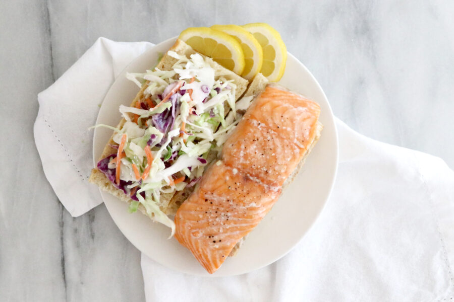 Salmon sandwich on white plate in center of photo sitting on top of a white napkin.