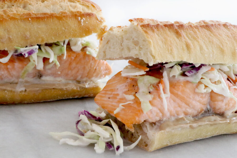 two salmon sandwiches in entire photo topped with a coconut citrus slaw