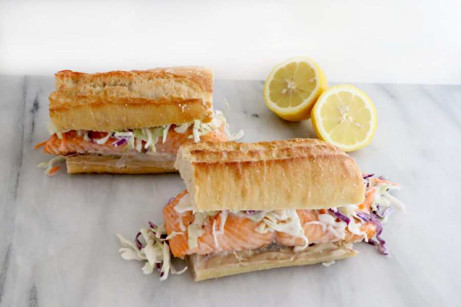 two salmon sandwiches in photo topped with a coconut citrus slaw. Sliced lemon on the right side above sandwich.