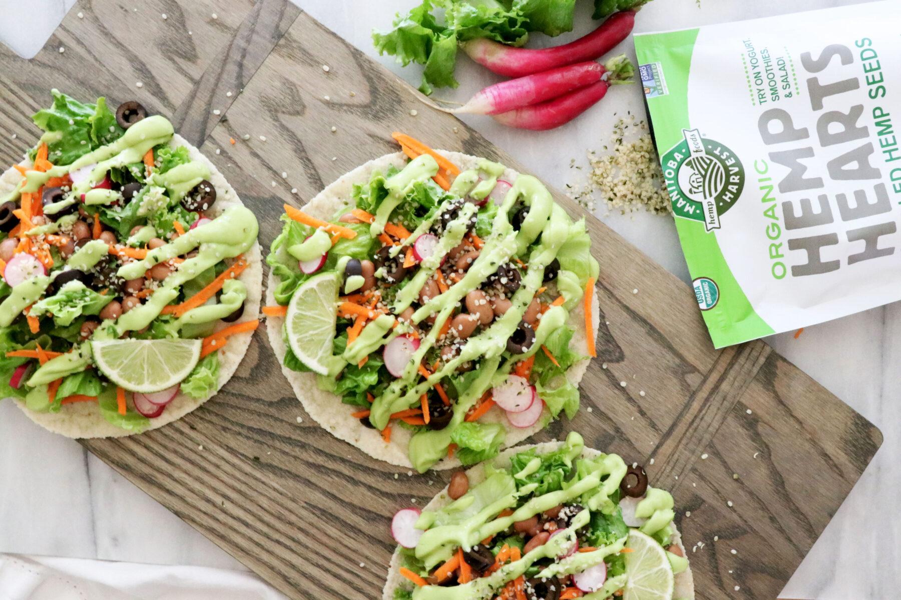 Three salad tacos on top of cutting board. Hemp hearts in top right corner.