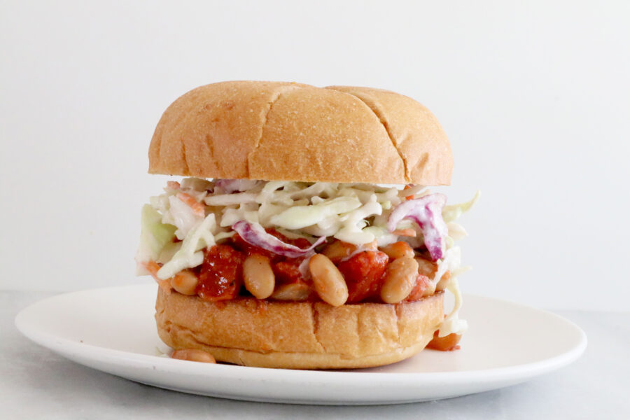 BBQ Bean Sloppy Joe Sandwich in the center of photo on top with white plate.