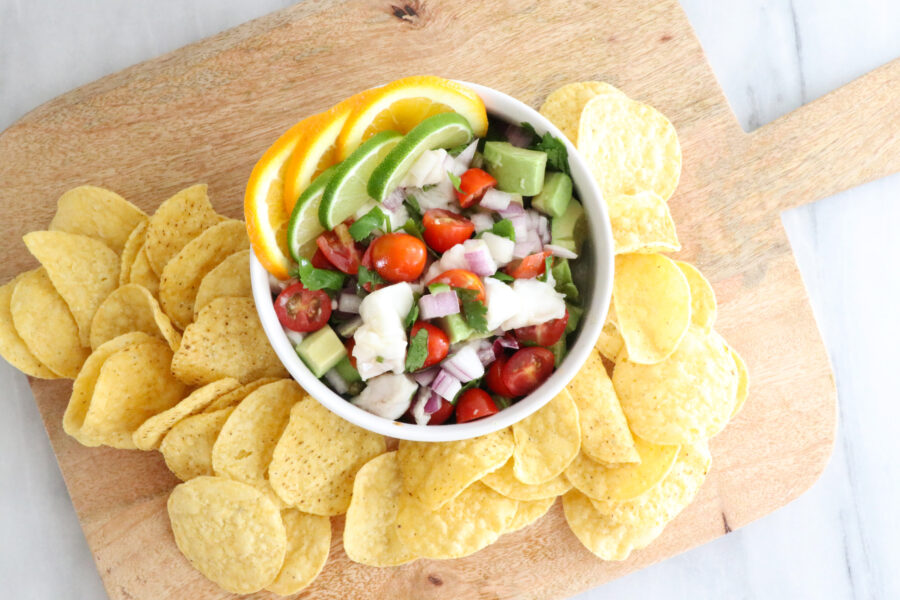 White bowl of halibut ceviche in center of photo with lime and orange wedges on top. Tortilla chips surrounding bowl on wooden cutting board.