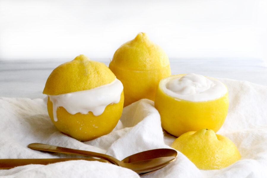Three lemons with tops cut off and filled with coconut cream. Sitting on white napkins with two spoons at the bottom of photo.