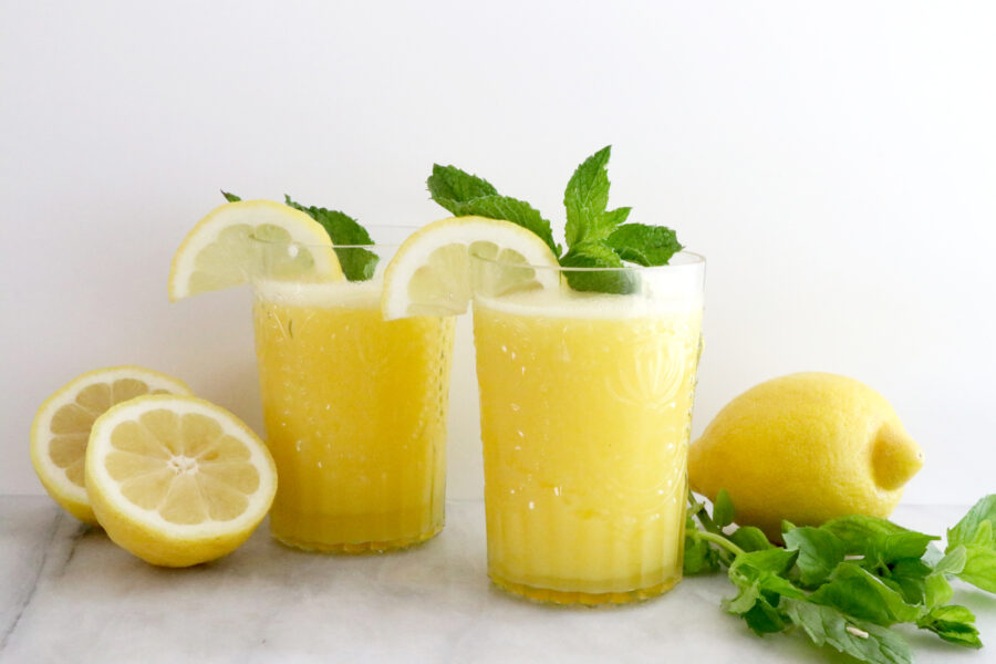 Two glasses full of blended frozen lemonade with a lemon on each side and basil on the right side.