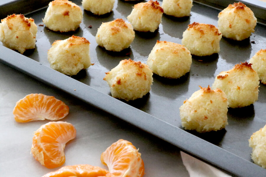 Baking tray filled with orange coconut macaroons on the right and clementine slices on the left.