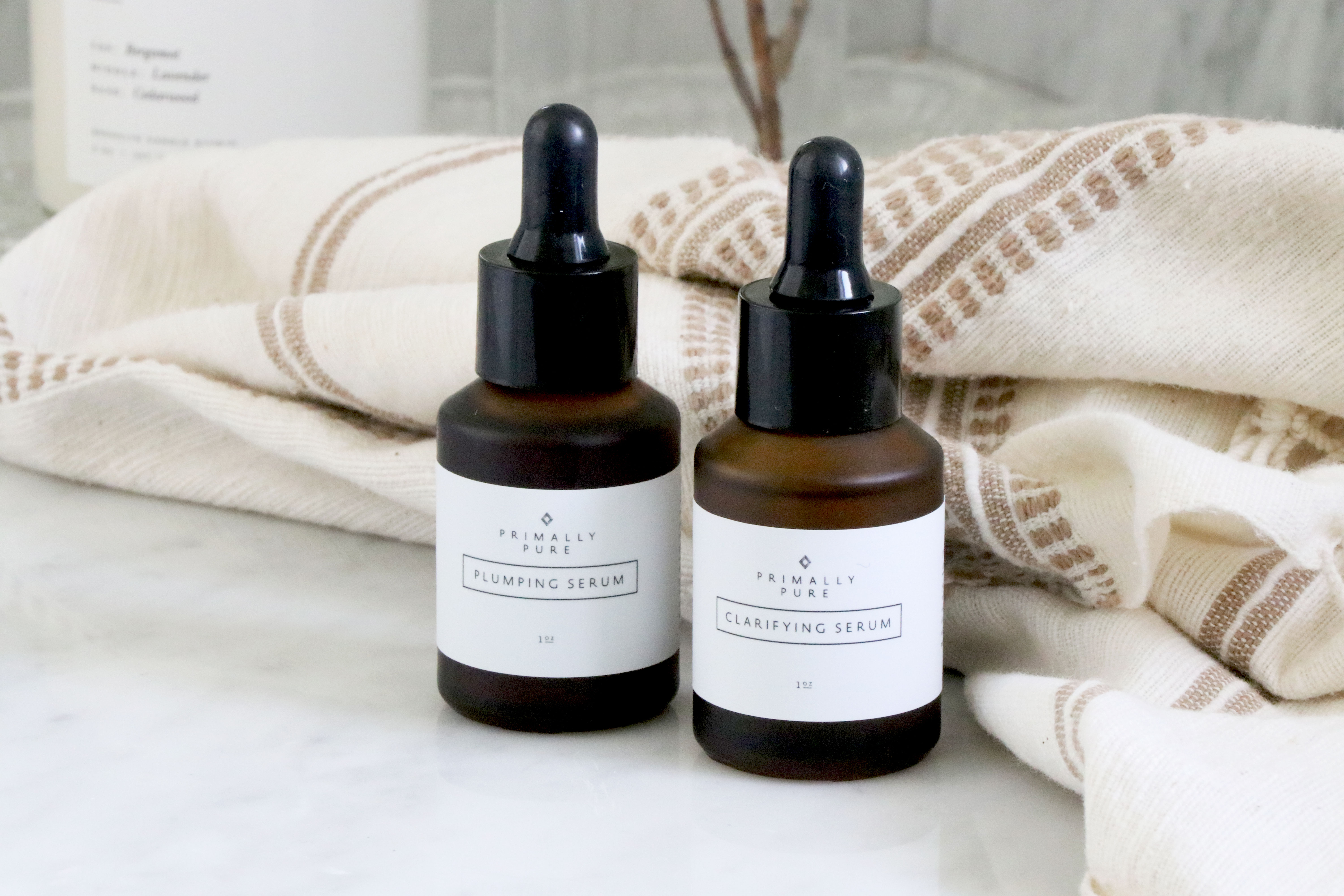 two bottles of Primally Pure serum on counter top with towel in the background.