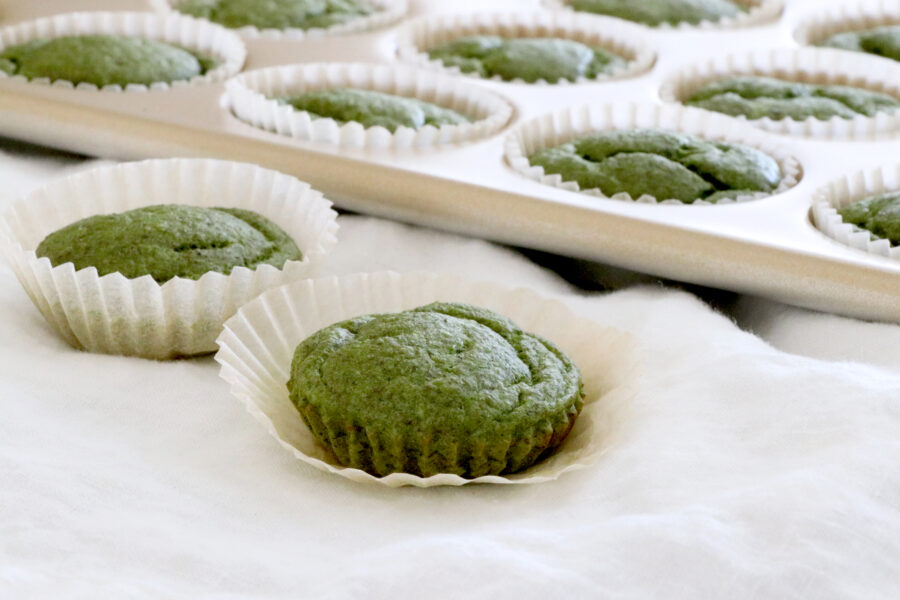 Two spinach muffins in front of photo with muffin tin in background with spinach muffins.