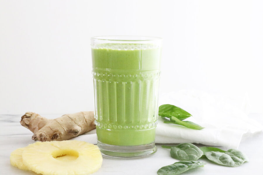 Glass filled with tropical greens protein smoothie in center of photo with fruit on the left of glass and spinach on the right.