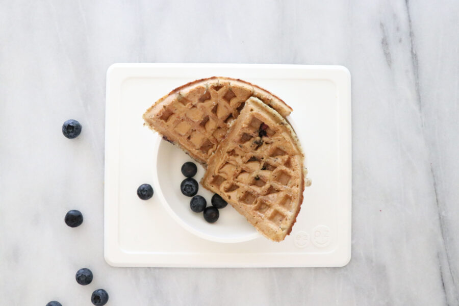 White plate with two waffle squares and blueberries.