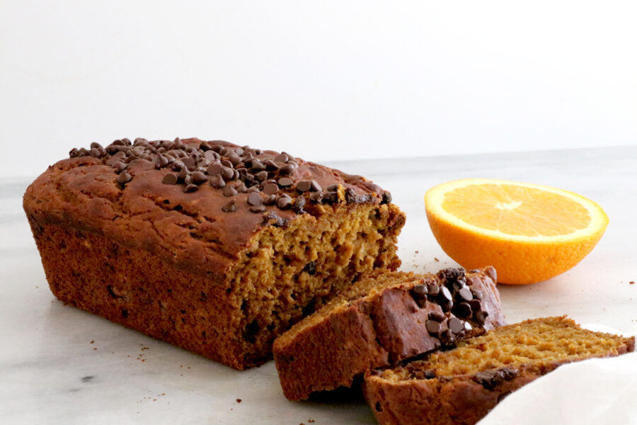 Loaf of orange pumpkin chocolate bread with chocolate chips on top. Two slices and half an orange on the right side.
