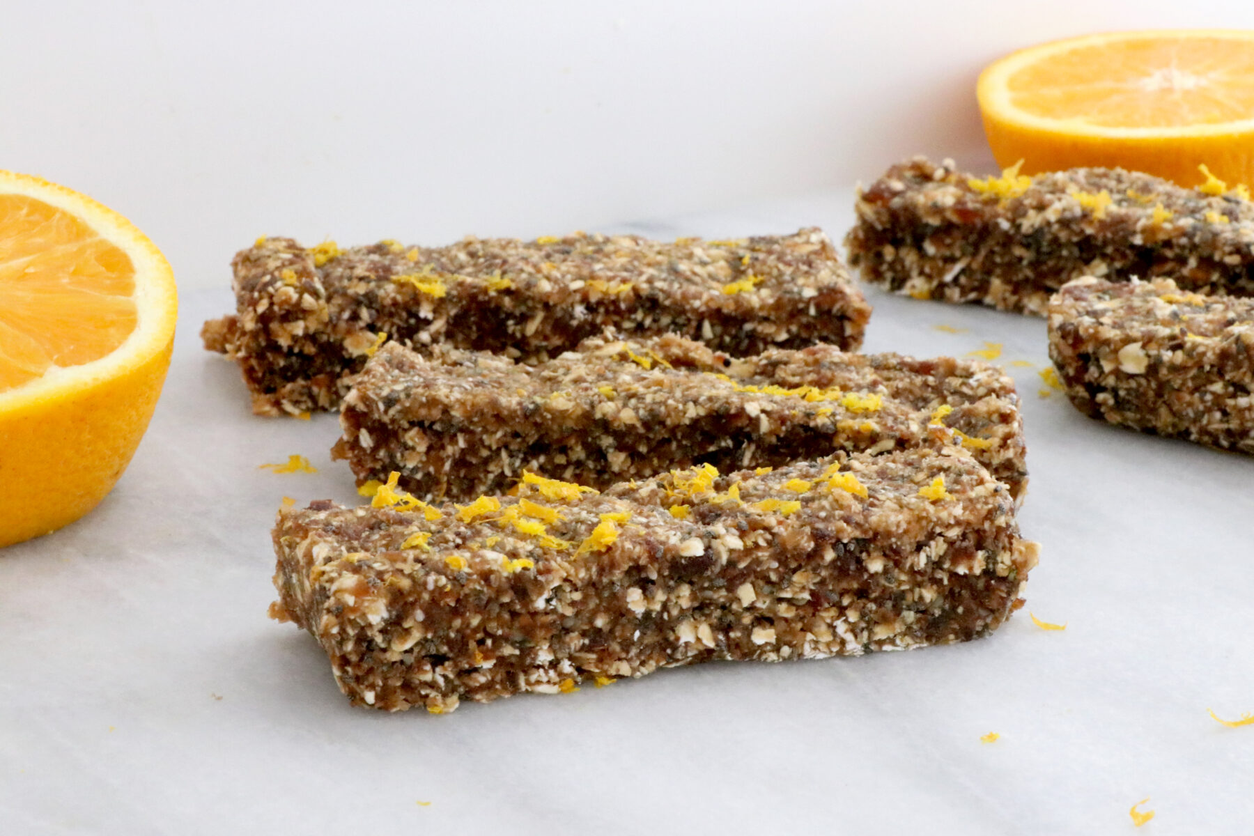 3 energy bars filled with dates, oranges and oats in center of photo. Orange slices on each side.