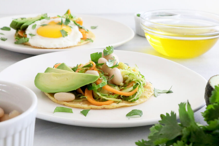 White plate with taco topped with Brussels sprouts, sliced avocado, white beans and parsley. Olive oil and parsley in the background.