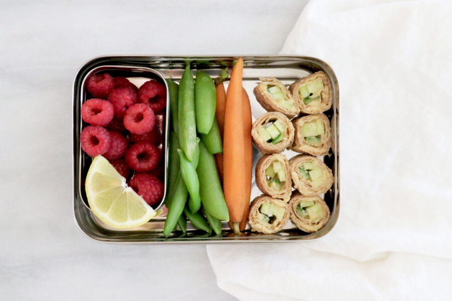 Lunchbox filled with hummus tortilla roll ups, carrots, green snap peas, raspberries and lemon slices.