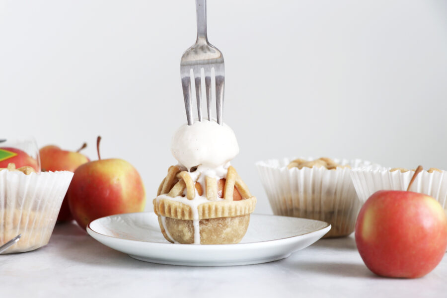 White plate with mini apple pie, vanilla ice cream and fork sticking out on top. Apples placed on both sides of pie.