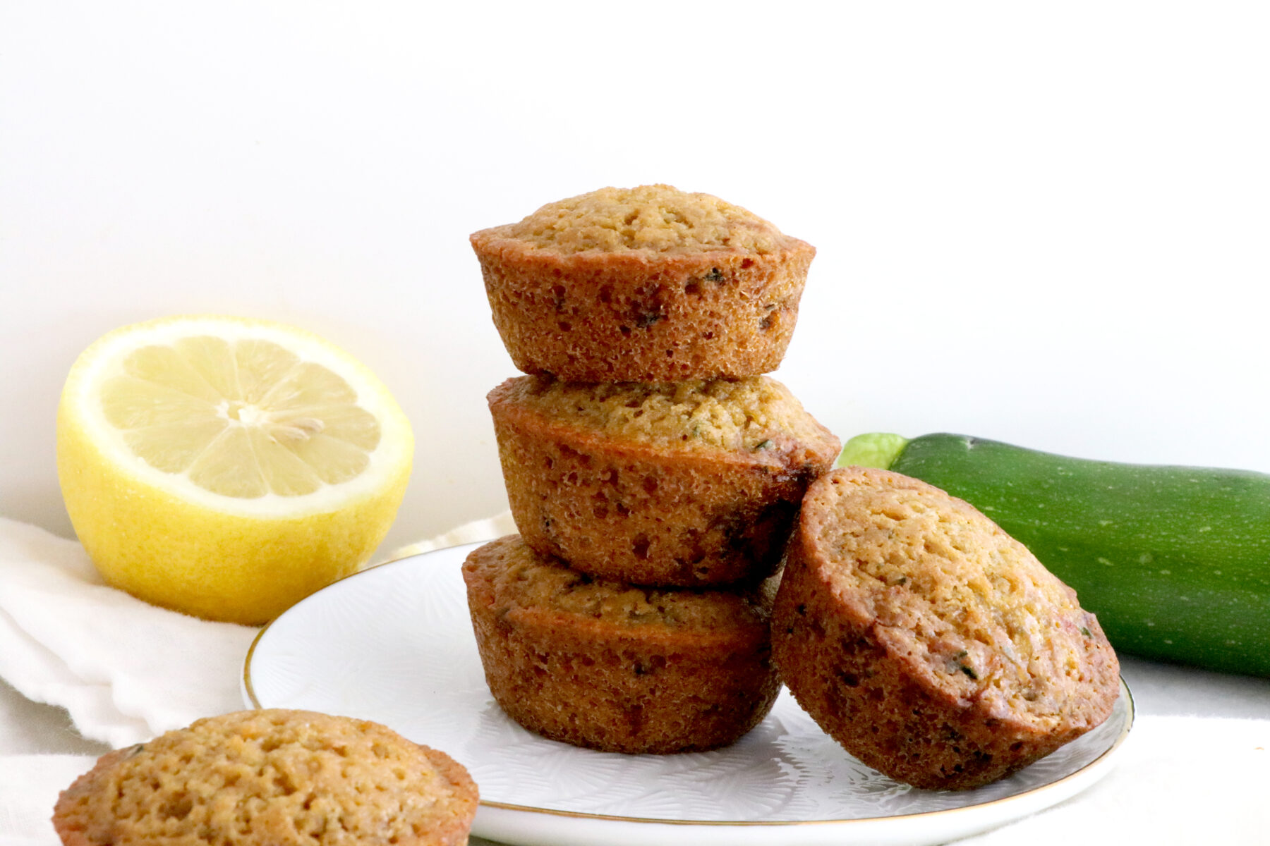 Three zucchini muffins stacked on top of each other with one leaning on the side all on a white plate. Zucchini and lemon in background.