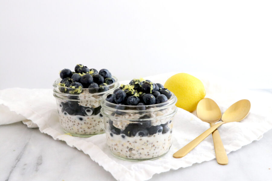 Two glass jars filled with layers of overnight oats and fresh blueberries. Two gold spoons on the side with a lemon.