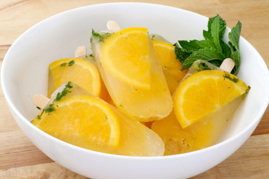 White bowl filled with orange ginger mint popsicles.