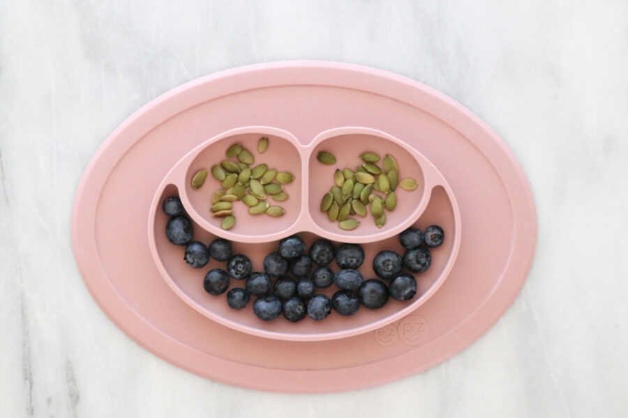 Pink Toddler plate filled with blueberries and pumpkin seeds.