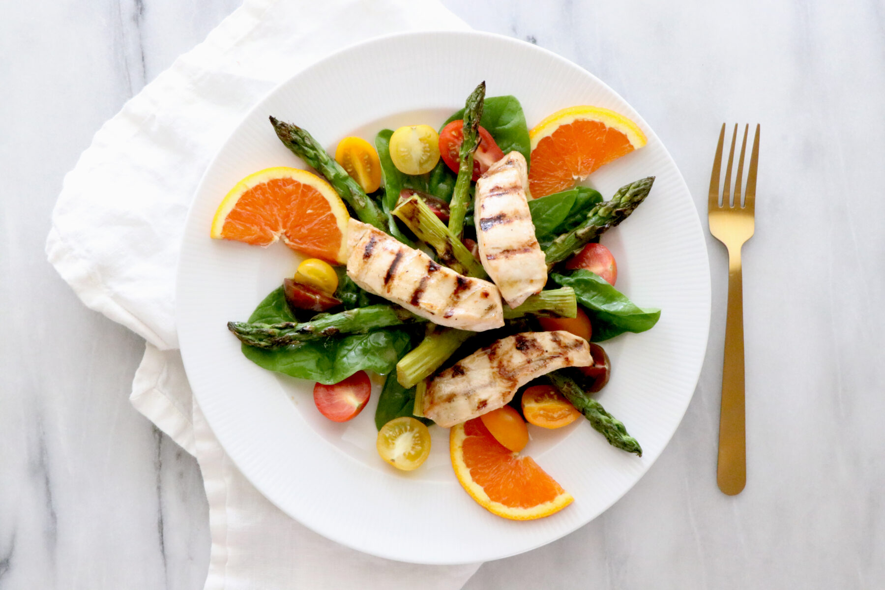 White plate of salad topped with asparagus, orange slices, tomatoes and grilled chicken. Gold fork on the right.