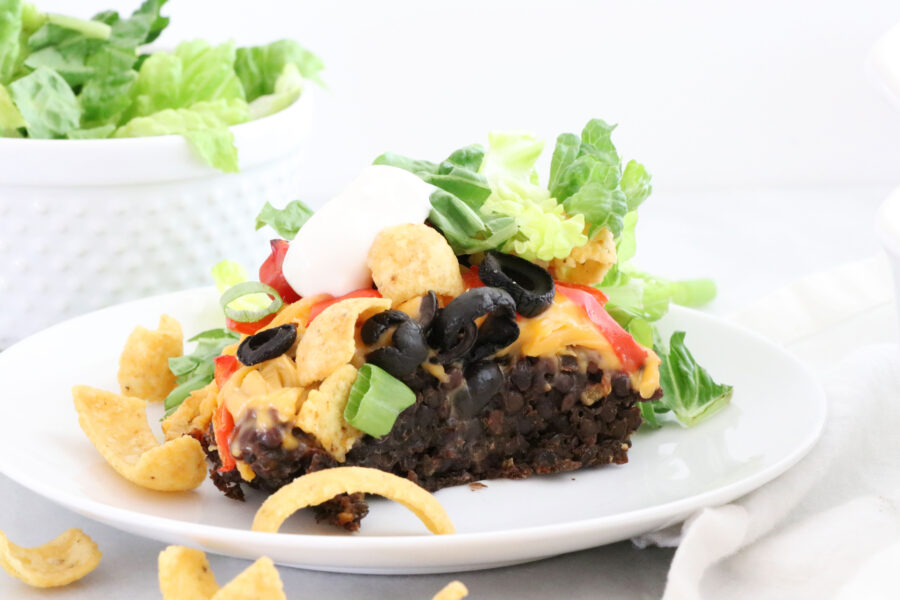 White plate with taco salad casserole topped with corn chips, tomatoes and lettuce.