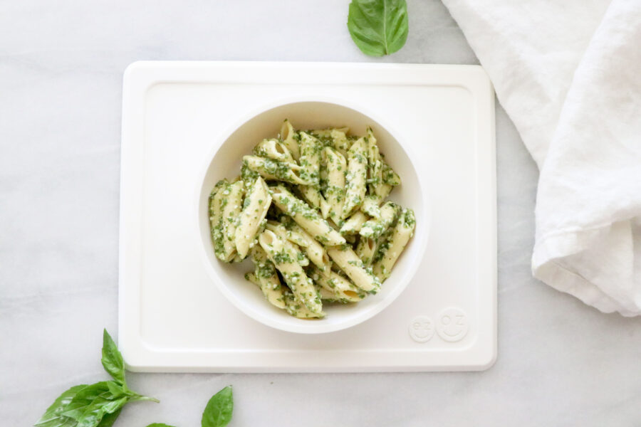 White toddler plate filled with pesto pasta and basil leaves around plate with white napkin on the right.