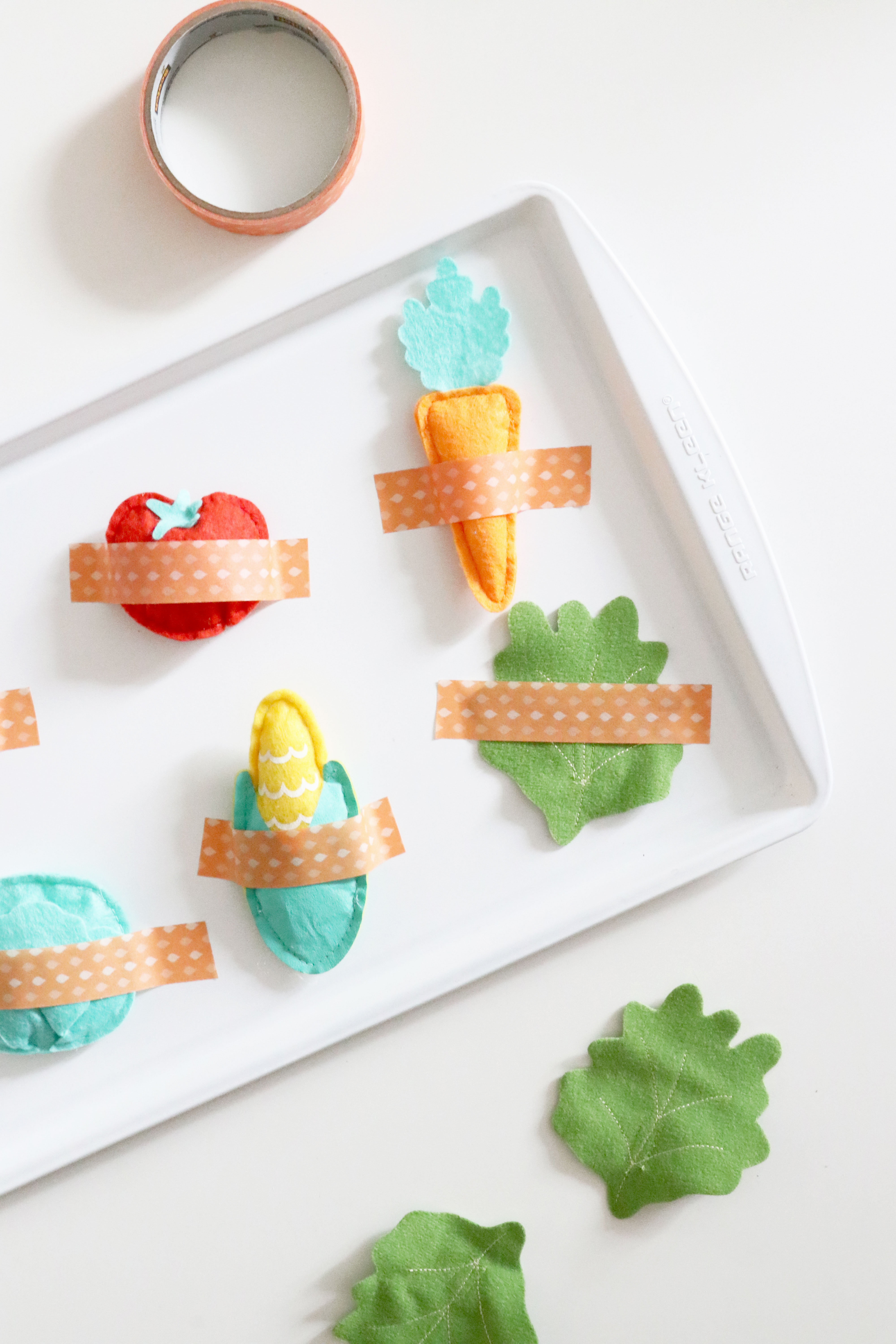 Plush Toy Vegetables Taped Onto Baking Sheet For Toddler Activity. Toddlers can remove the tape and toys!