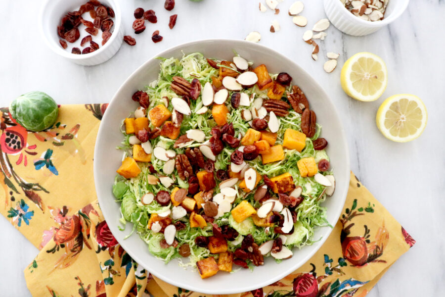 Large white bowl filled with Brussels sprouts butternut squash salad with cranberries all on a colorful napkin. Lemons and cranberries on the side.
