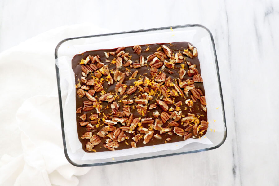 Clear pan with chocolate orange fudge topped with pecans and orange zest