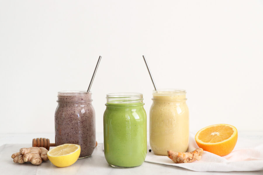 Three mason jars filled with different types of smoothies. Sliced oranges, lemons and ginger around smoothies.