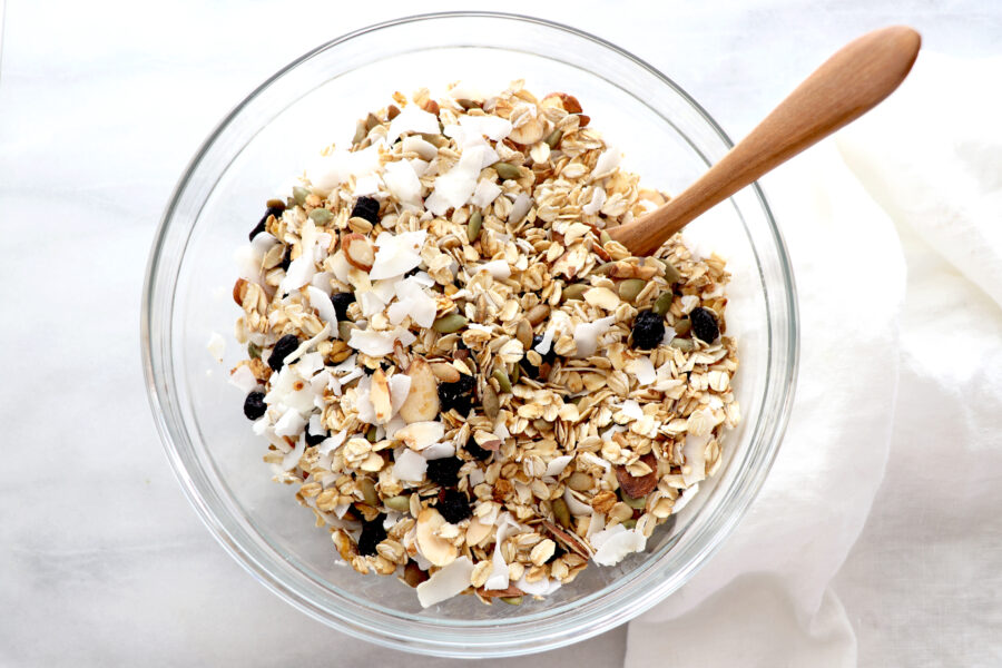 Clear glass bowl filled with muesli that containers oats, blueberries, shredded coconut pumpkin seeds, almonds and lemon.