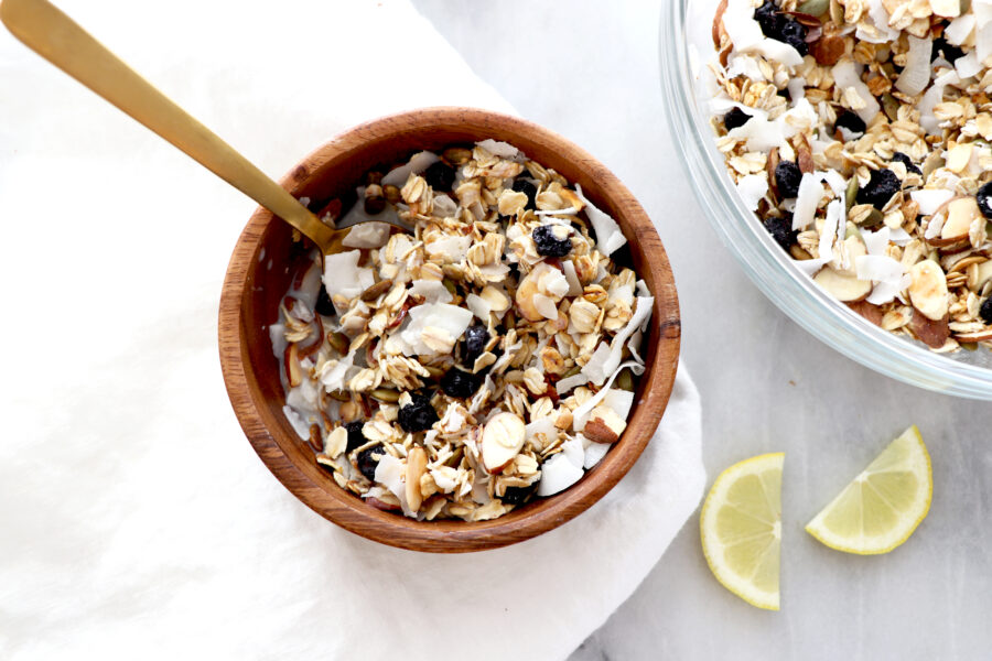 wooden bowl filled with muesli that containers oats, blueberries, shredded coconut pumpkin seeds, almonds and lemon.