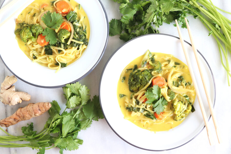 Two white bowls filled with turmeric noodle soup and veggies surrounding soup.