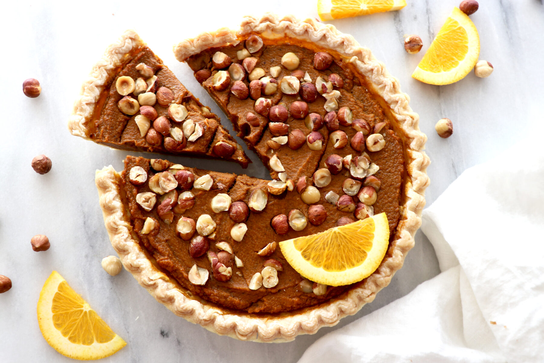 Orange hazelnut pumpkin pie topped with hazelnuts, orange slice and slice cut out. Surrounded by hazelnuts and orange slices.