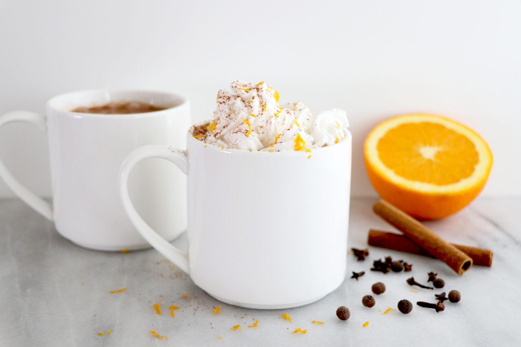 White mug with orange spiced hot coco topped with whipped cream. Surrounded by orange slice and spices.