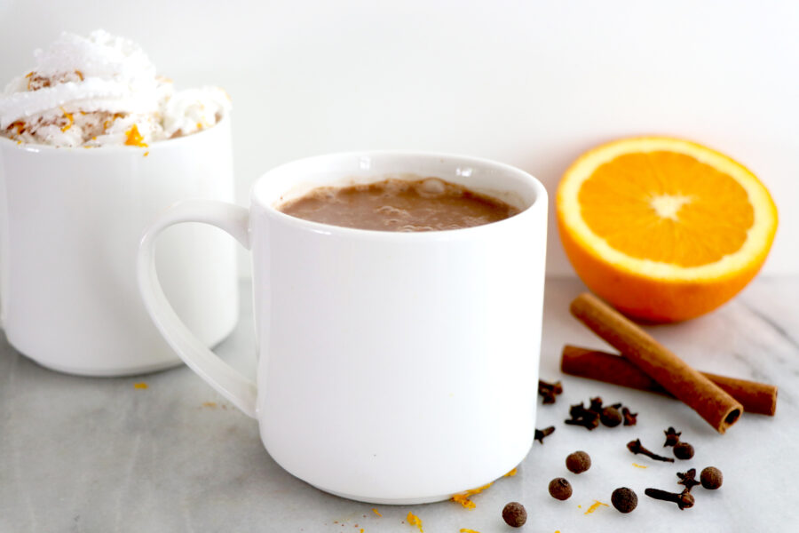 White mug with orange spiced hot coco. Surrounded by orange slice and spices.