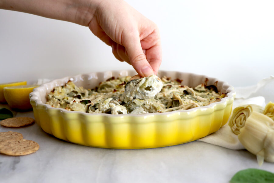 Yellow dish filled with artichoke dip and hand taking a scoop of dip with cracker.