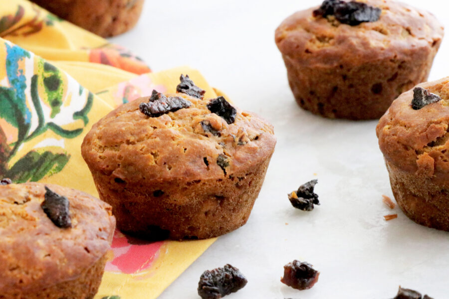 Five gingerbread prune muffins across photo with diced prunes on top. Floral napkin on the left side.