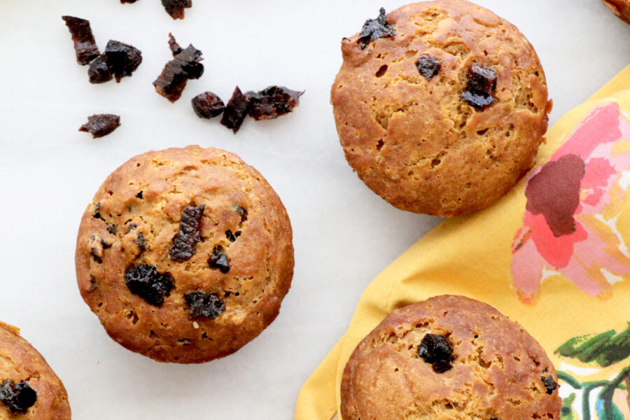 Four gingerbread prune muffins across photo with diced prunes and floral napkin on the side.