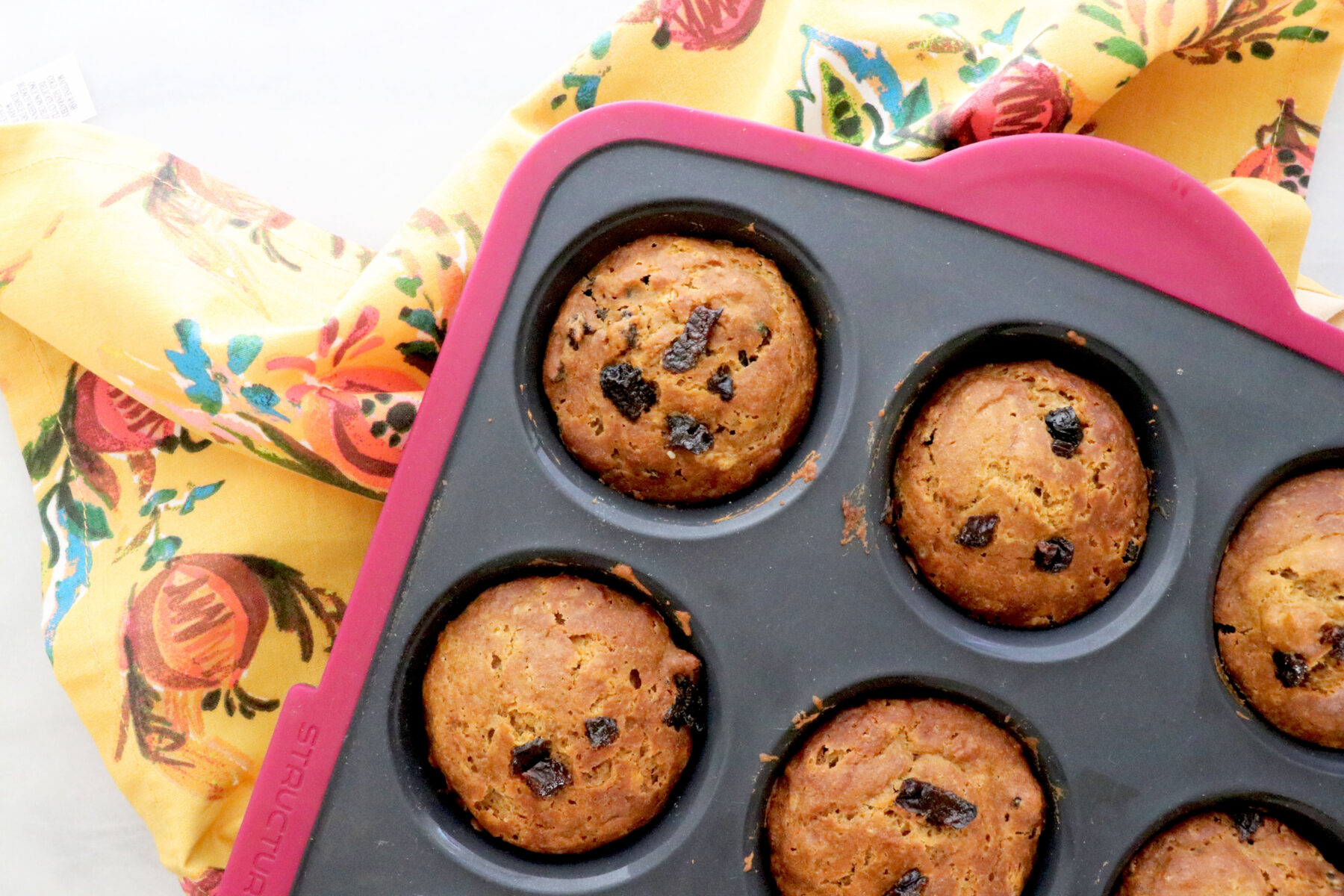 Muffin tin filled with gingerbread prune muffins all on a floral napkin and diced prunes on the side.