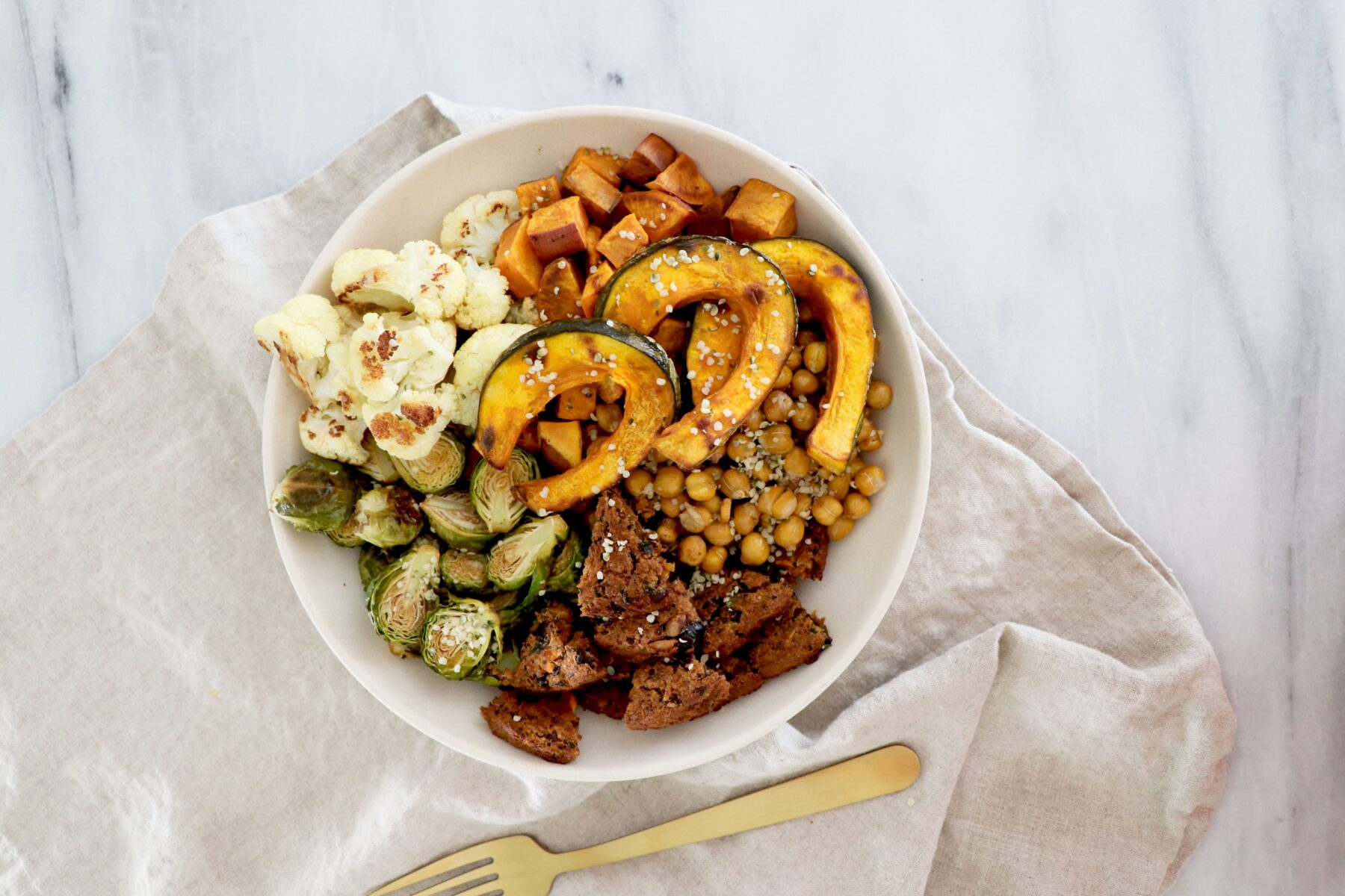 White bowl with squash, veggie burger, Brussels, sweet potato and cauliflower.