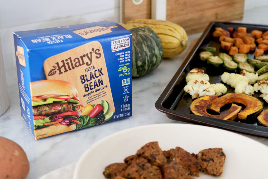 Hilary's black bean burger box on left side, white plate with bean burgers and tray with roasted veggie.