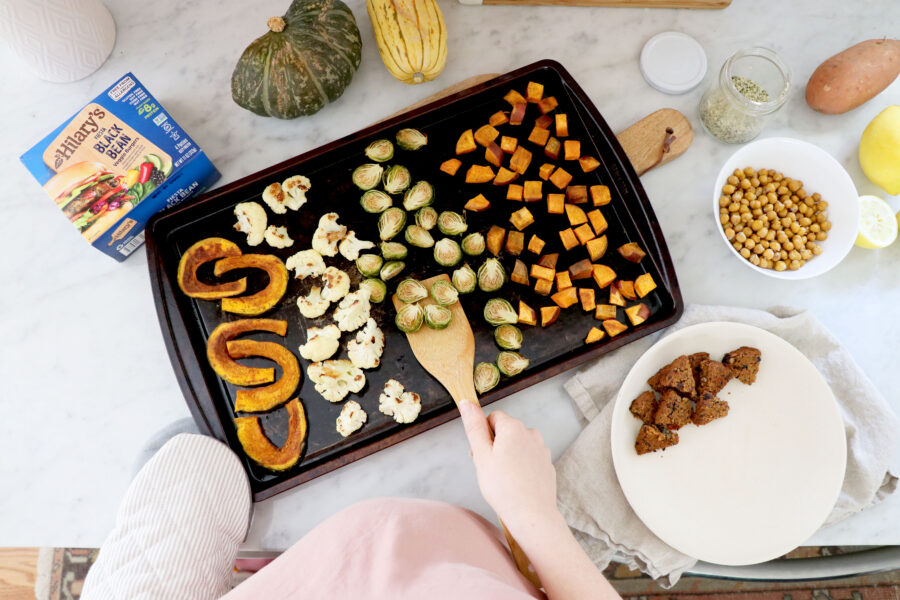 Grey tray with roasted veggies, wooden spoon and person holding spoon.