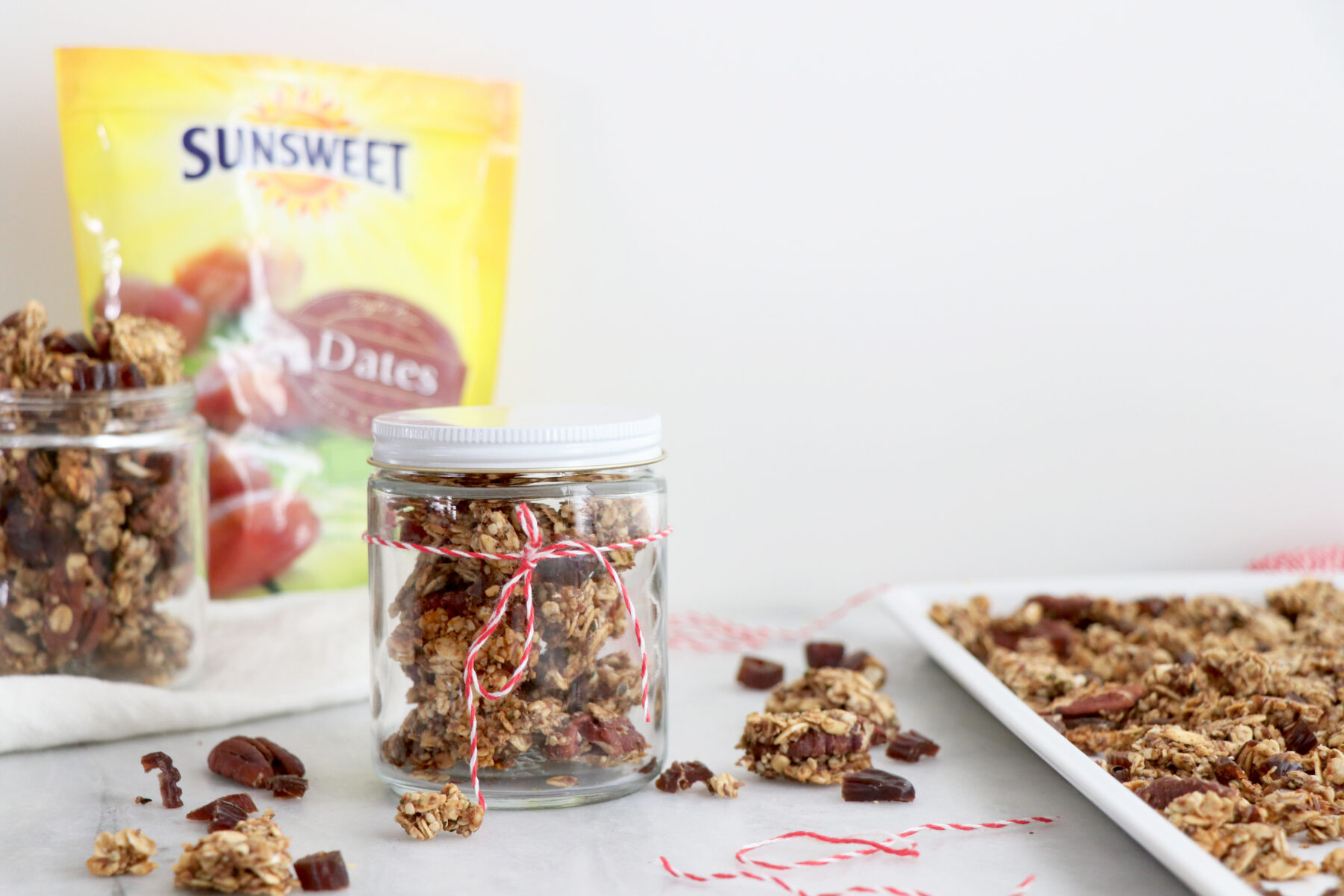 DIY Homemade Granola in Glass Jar with Red Ribbon and Package of Sunsweet Dates in Background